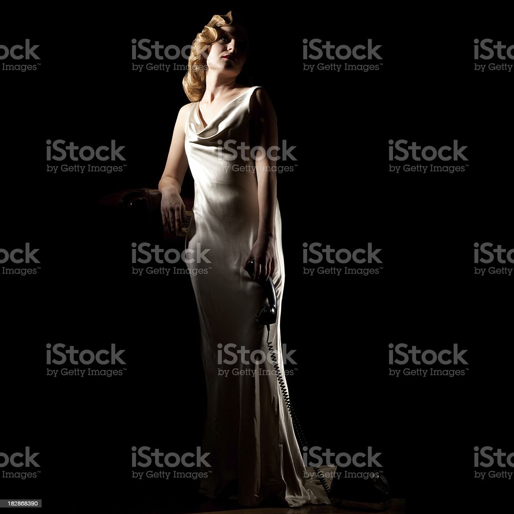 Full Body 1940's Woman Dangles Phone. Film-noir Retro Styling. stock photo