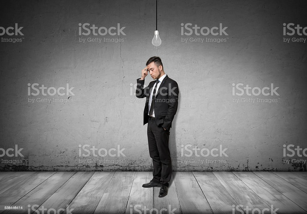 Full body of businessman stands and thinks with turned-off stock photo