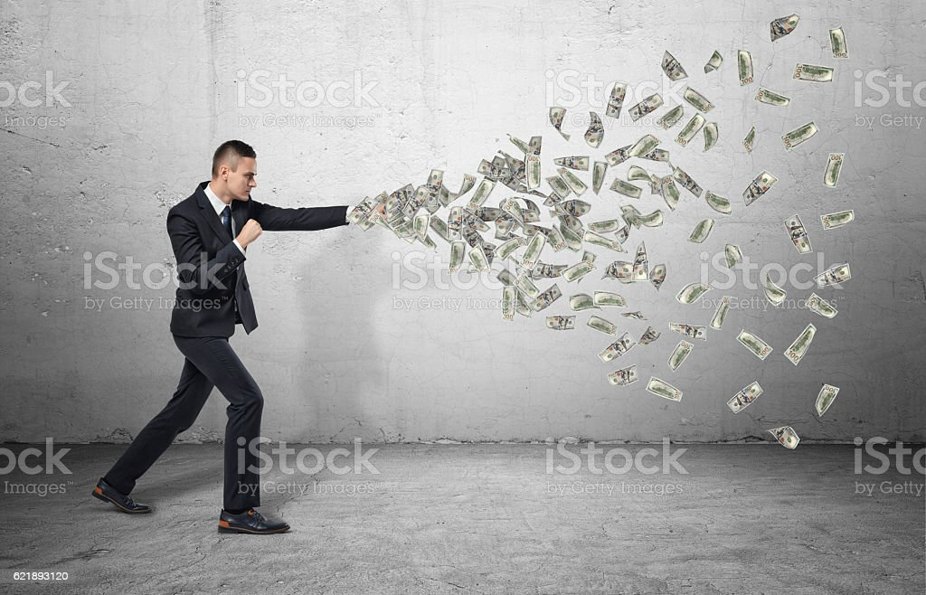 Full body of businessman strikes with his fist and banknotes stock photo
