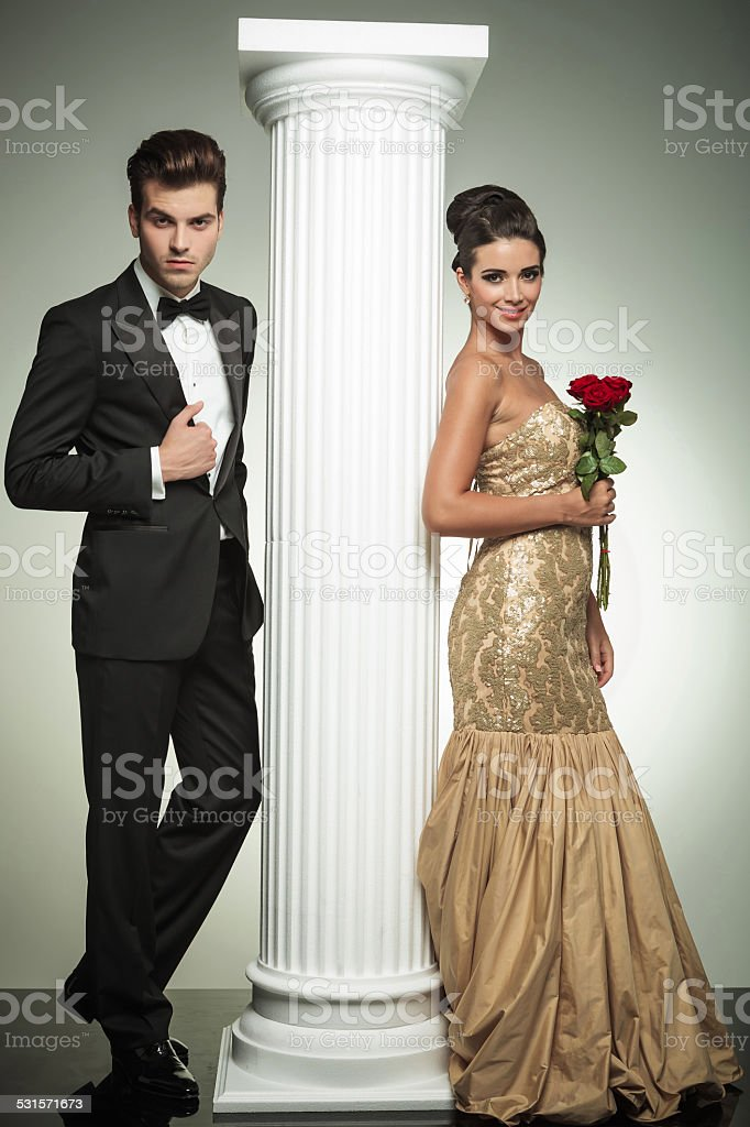full body picture of an elegant couple near column stock photo