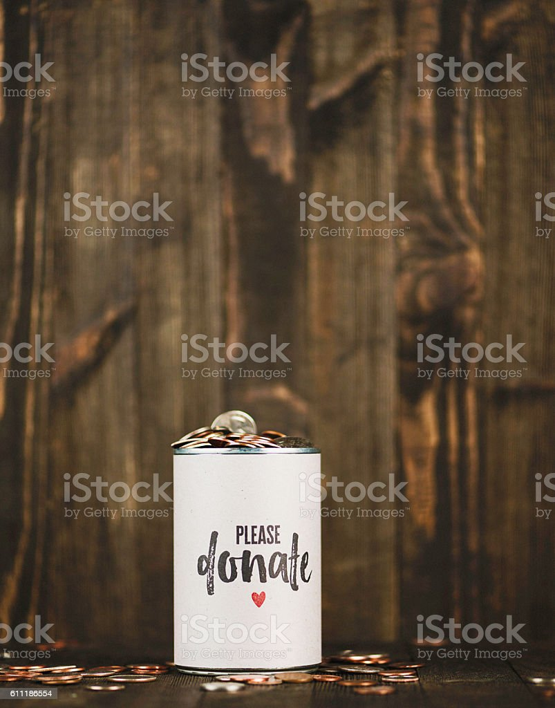 Full charity money can with copy space against wooden background stock photo