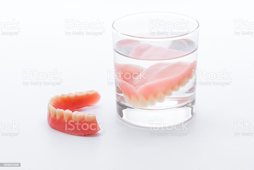 Full Denture in glass of water on white background stock photo