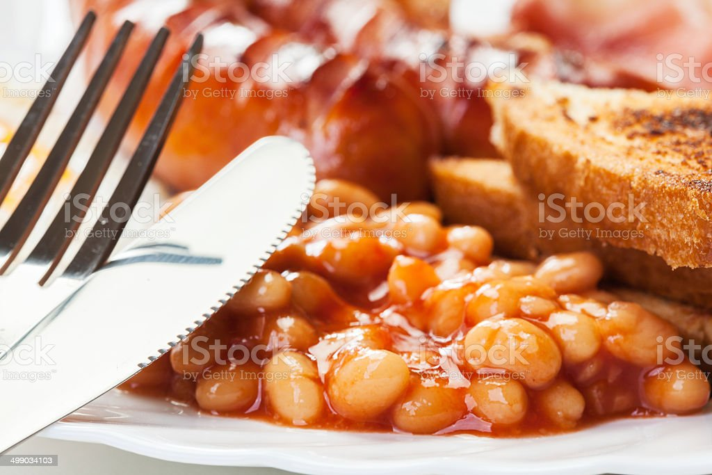 Full English breakfast with bacon, sausage, egg and baked beans stock photo