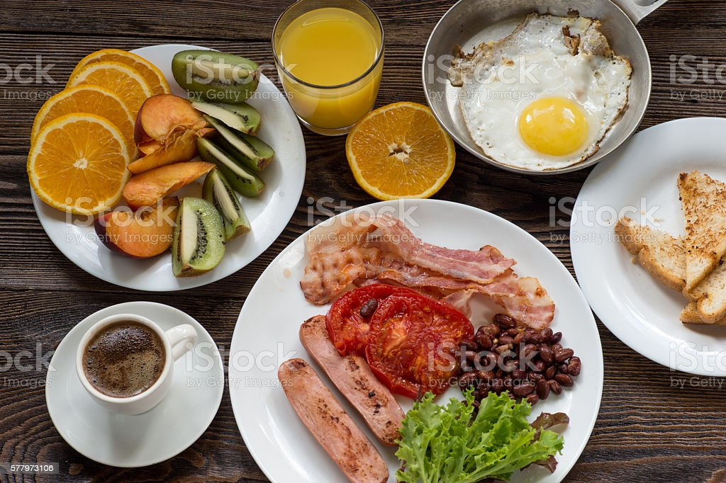 Full English breakfast with sausage, baked tomato, beans and toasts stock photo