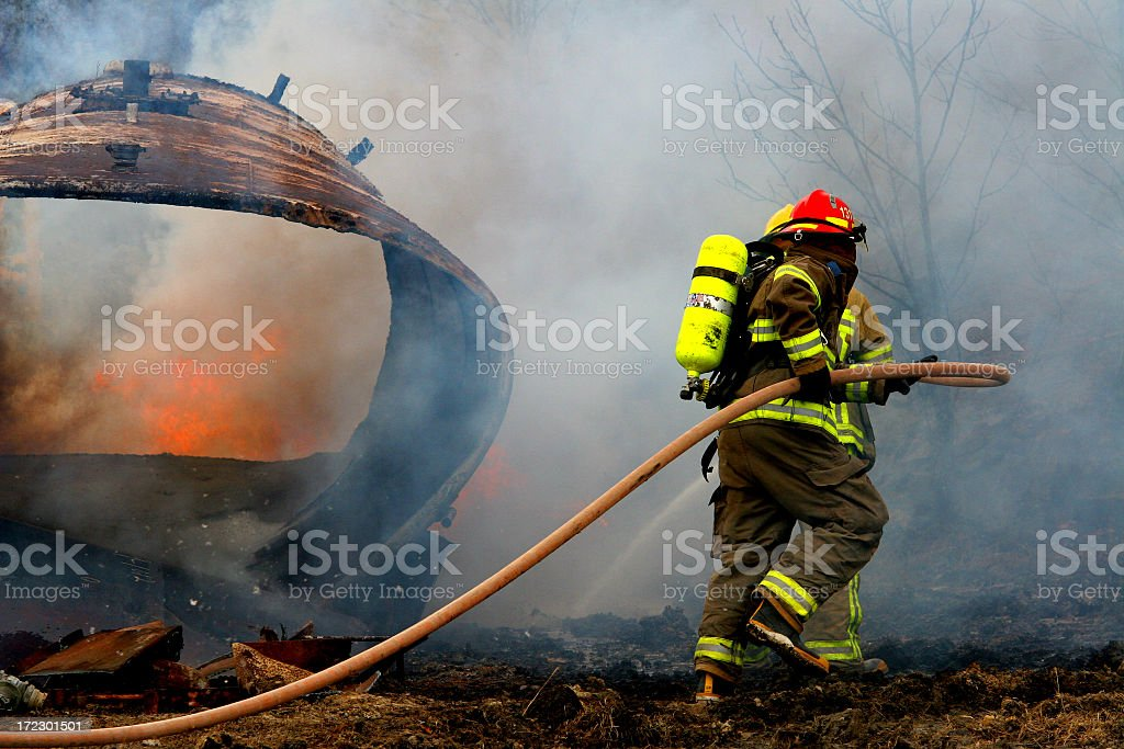 Full geared firefighter with water hose on field stock photo