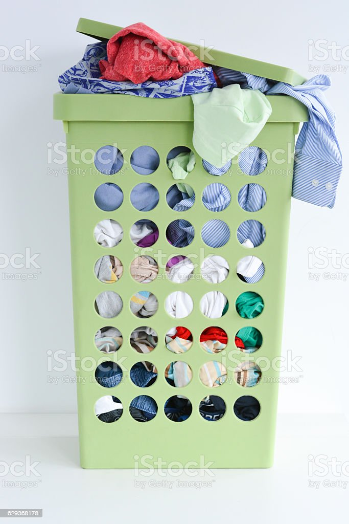 Full laundry basket with dirty clothes stock photo