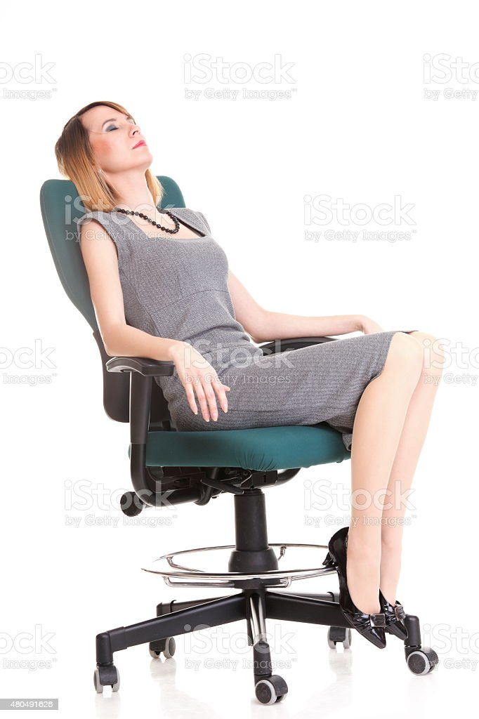 Full length business woman sitting on chair relaxing stock photo