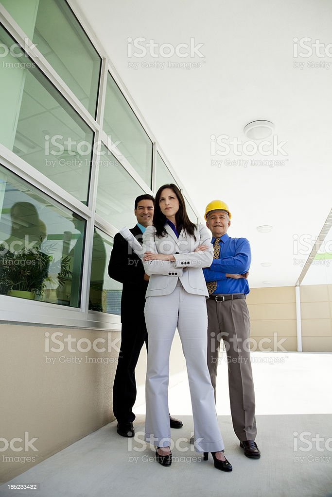 Full length businesswoman and two businessmen stock photo