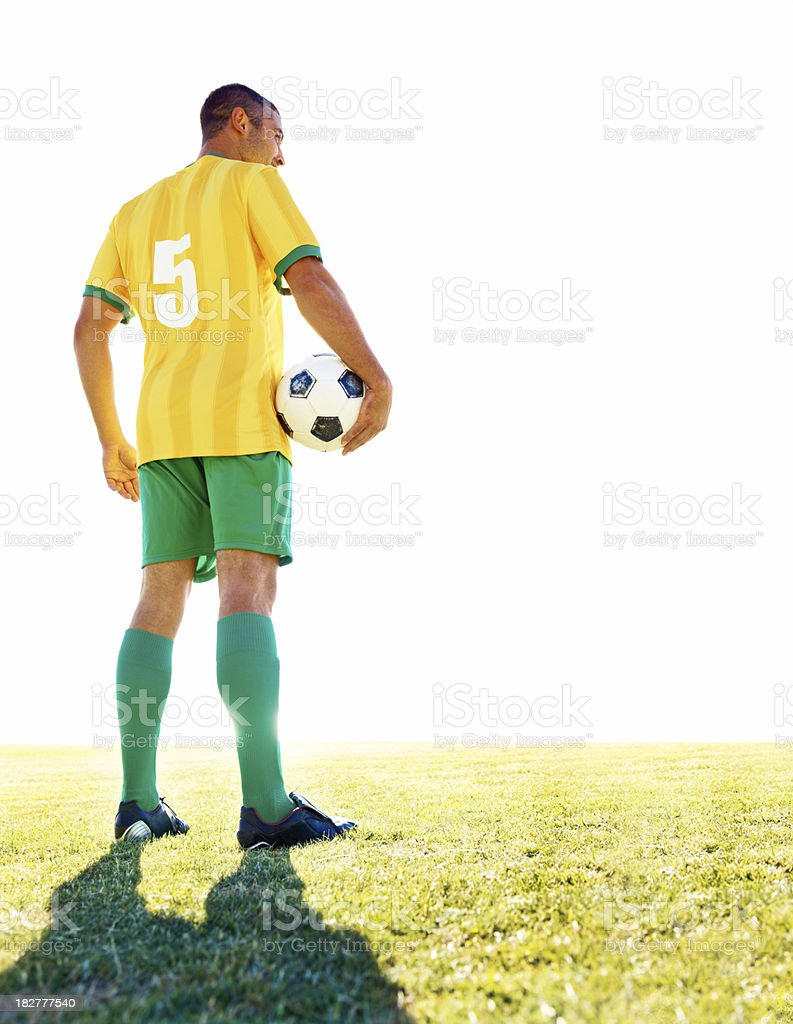 Full length of a footballer with ball on the field royalty-free stock photo