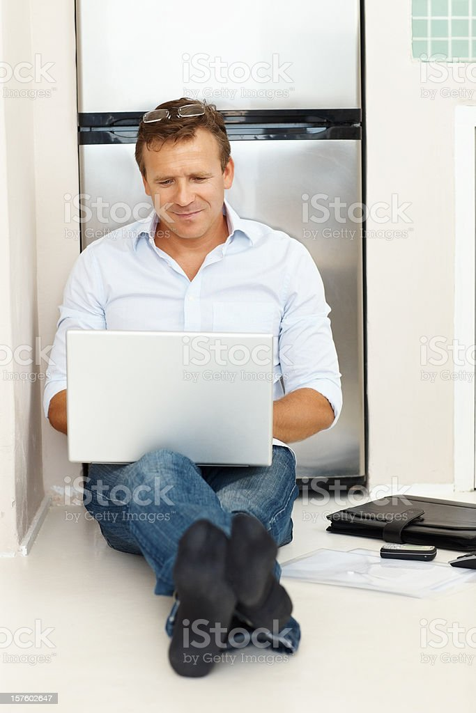 Full length of a mature guy working on laptop royalty-free stock photo