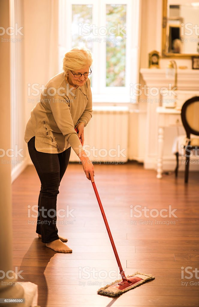 Full length of a mature woman cleaning the floor. stock photo