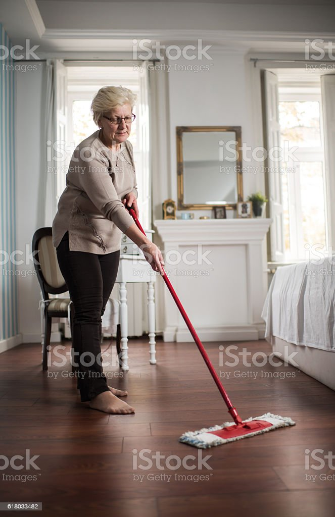 Full length of a senior woman cleaning the floor. stock photo