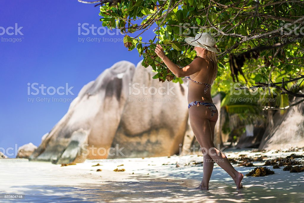 Full length of a smiling woman enjoying on the beach. stock photo