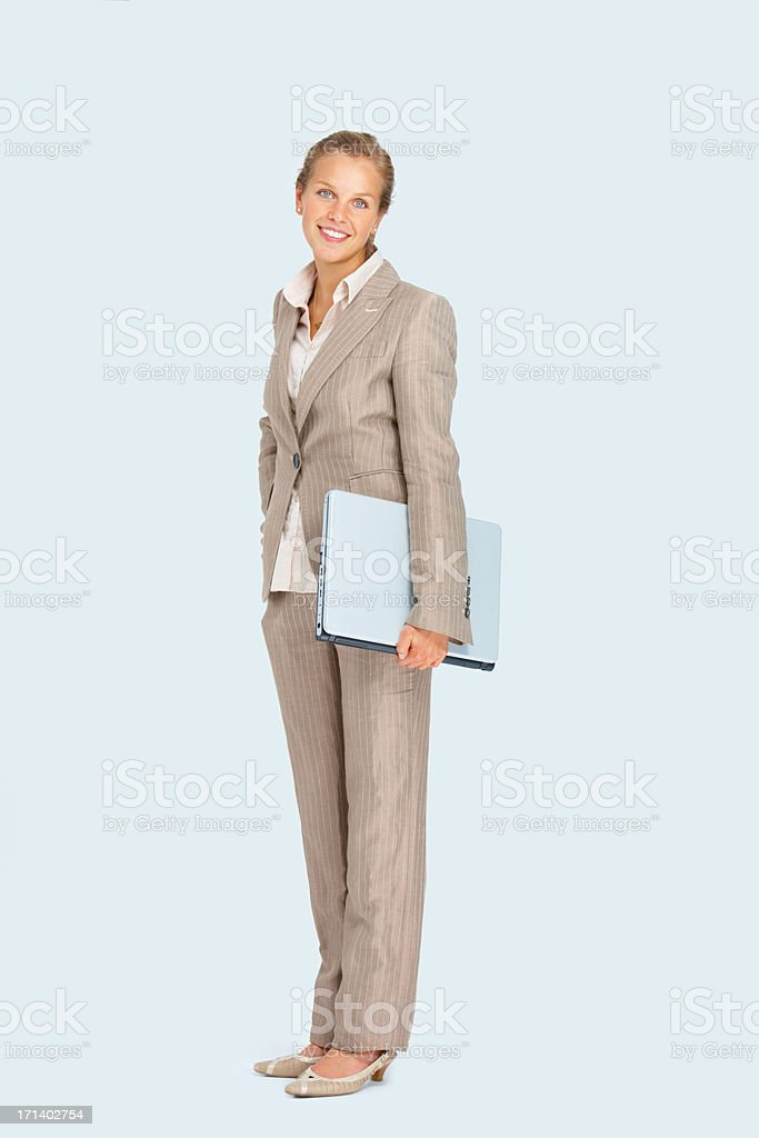 Full length of a young business woman holding a laptop royalty-free stock photo