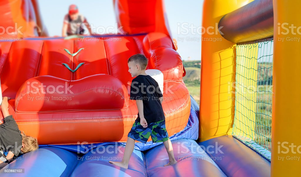Full length of boy playing on bouncy castle stock photo