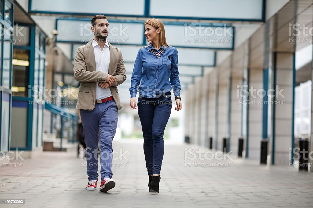 Full length of business colleagues walking together and communicating. stock photo