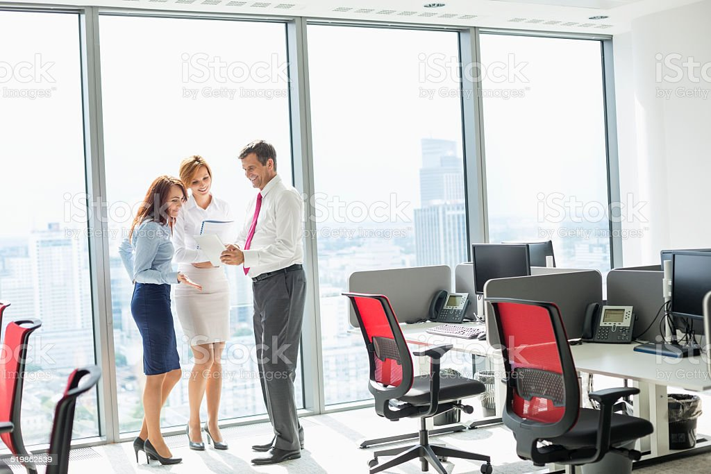 Full length of businesspeople discussing in office stock photo