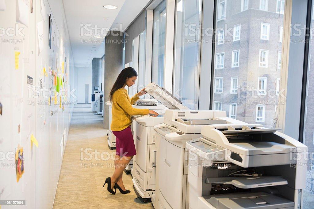 Full length of businesswoman using computer printer stock photo