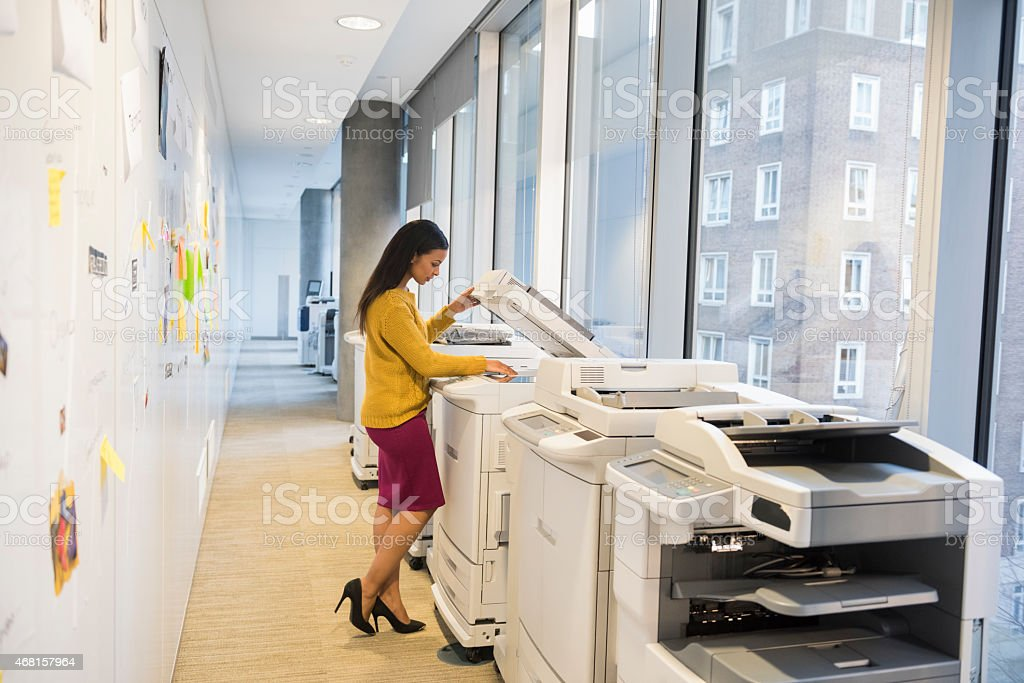 Full length of businesswoman using photocopier stock photo
