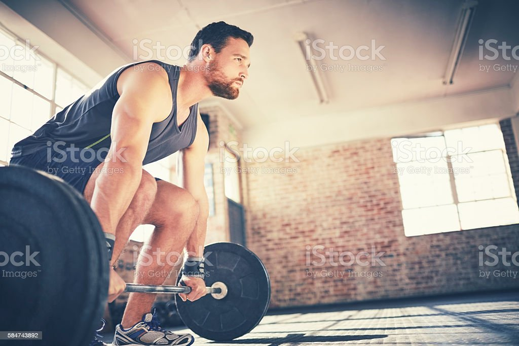 Full length of determined man lifting barbell in gym stock photo