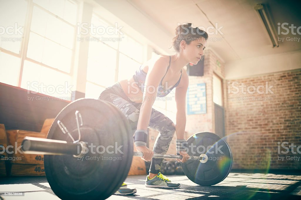 Full length of determined young female deadlifting barbell in gy stock photo
