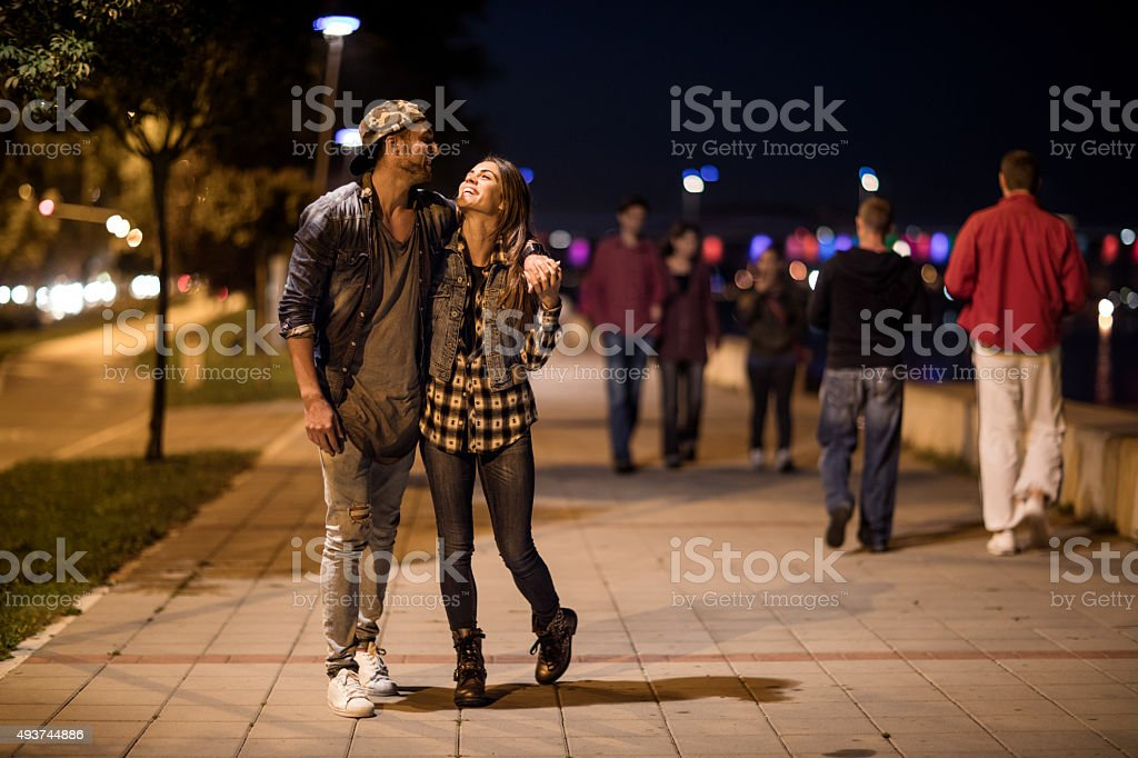 Full length of embraced couple walking on sidewalk at night. stock photo