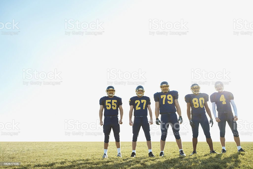 Full length of footballers in uniform against the bright sky royalty-free stock photo
