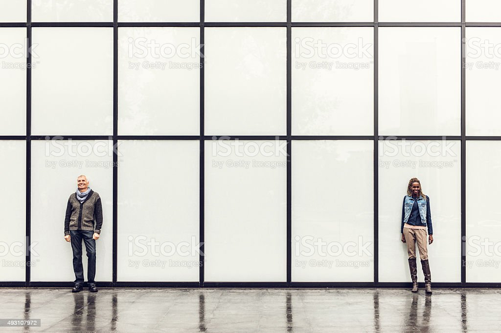 Full length of happy business people against rectangular curtain wall. stock photo