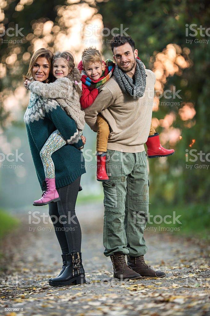 Full length of happy family piggybacking in the park. stock photo