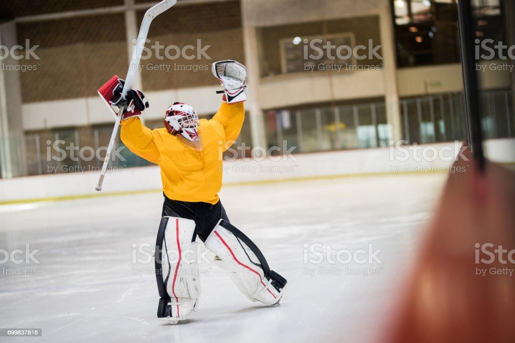 Full length of happy ice hockey goalkeeper celebrating his success at rink. stock photo