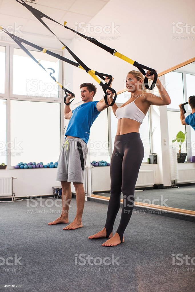 Full length of happy people stretching on Pilates class. stock photo