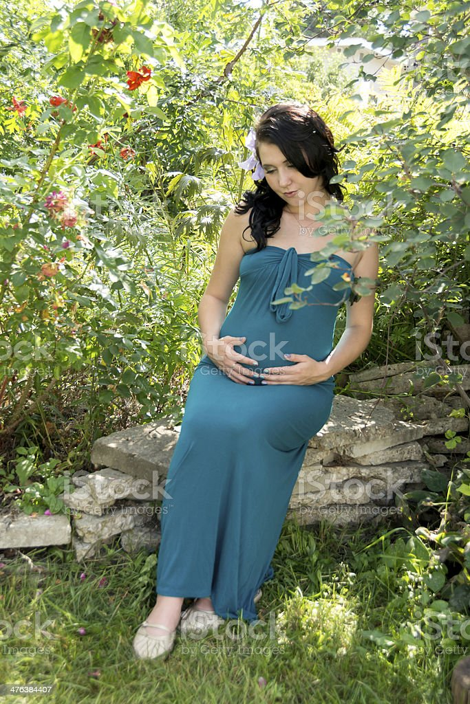 Full length of pregnant woman sitting in garden. royalty-free stock photo