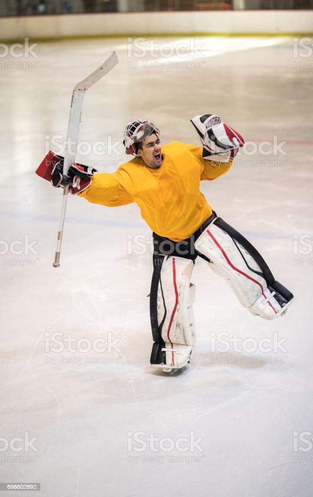 Full length of successful ice hockey goalie screaming of joy in a rink. stock photo
