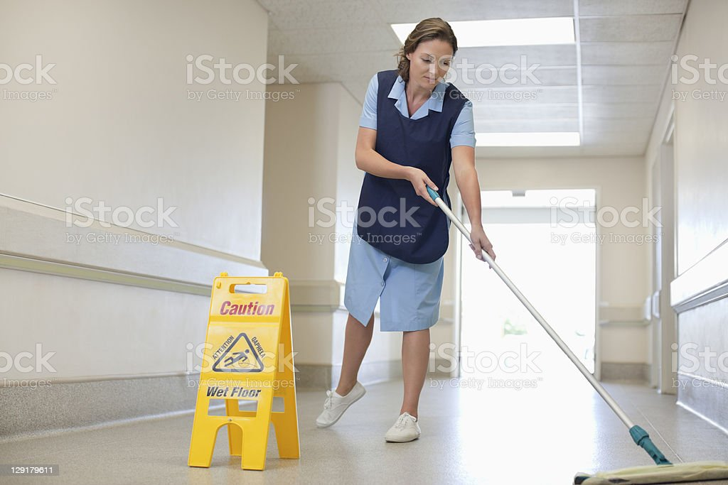 Full length of woman cleaning hospital floor stock photo