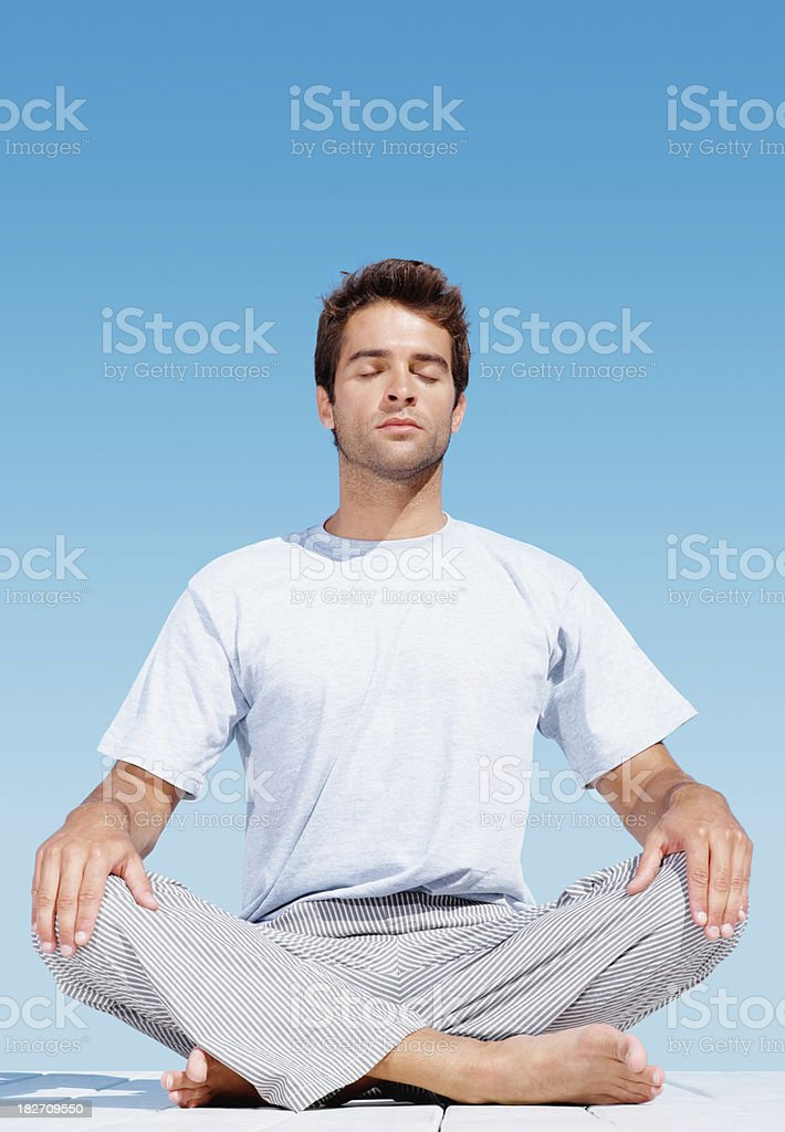 Full length of young guy meditating outdoors royalty-free stock photo