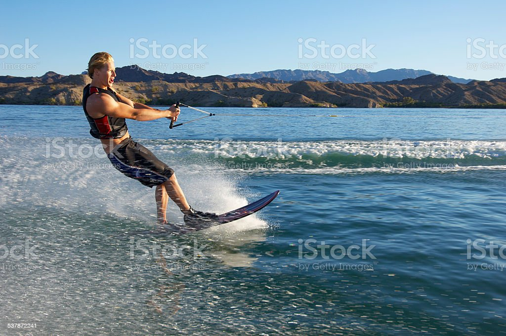 Full length of young man wakeboarding on lake stock photo