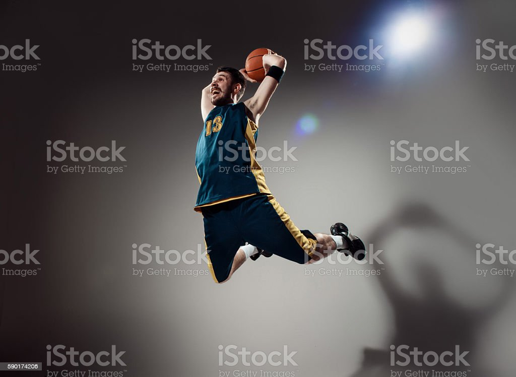 Full length portrait of a basketball player with a ball against gray...