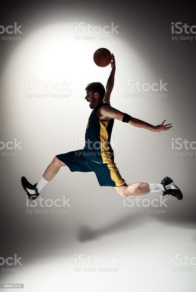 The silhouette view of a basketball player with a ball against gray...