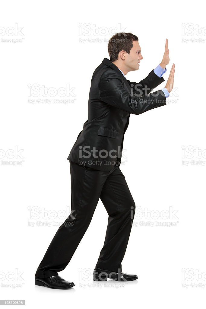 Full length portrait of a businessman pushing something royalty-free stock photo