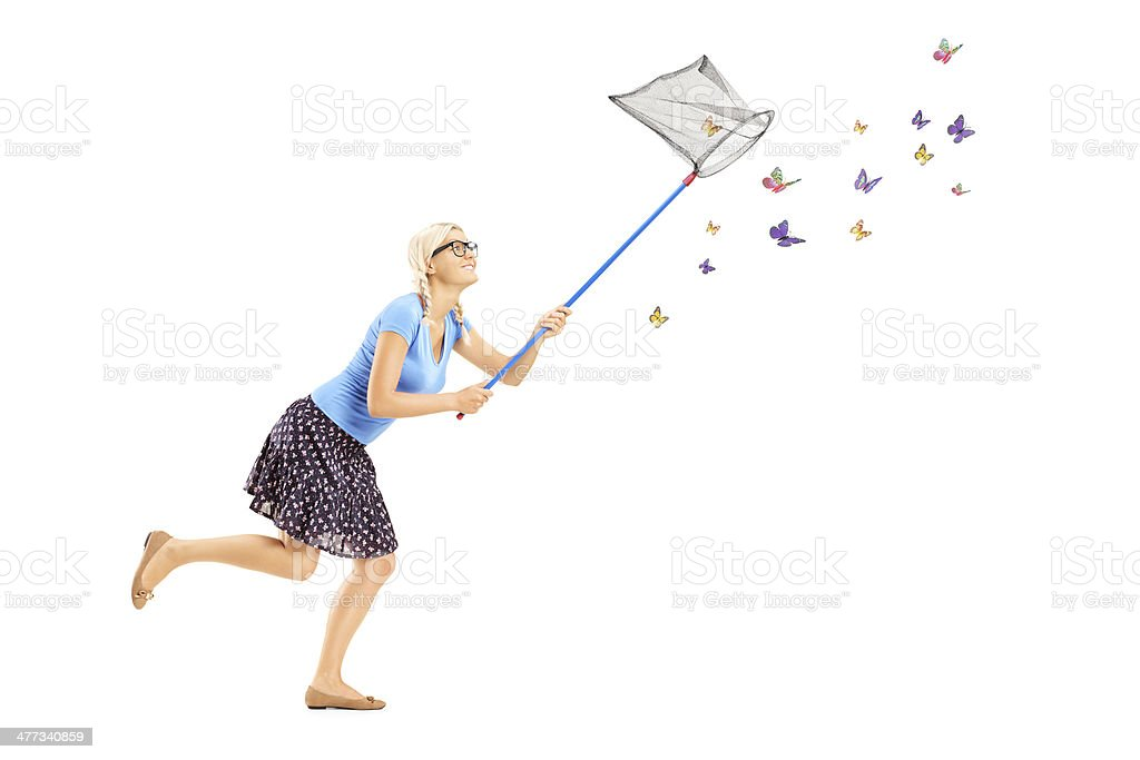 Full length portrait of a woman running and catching butterflies stock photo