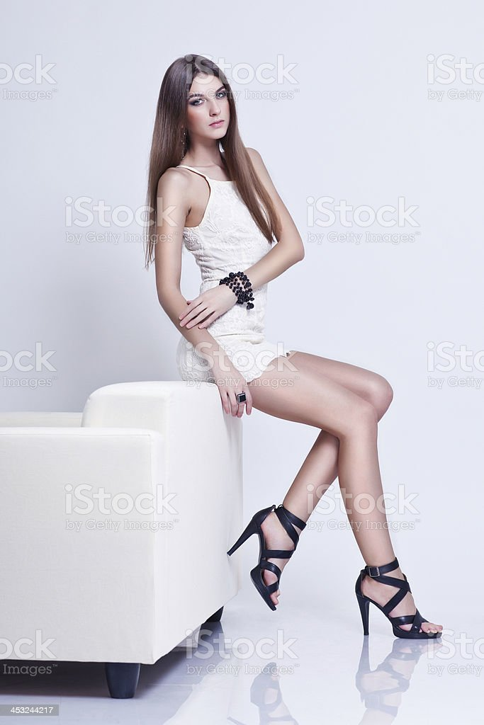 A full length portrait of a woman sitting on the couch royalty-free stock photo