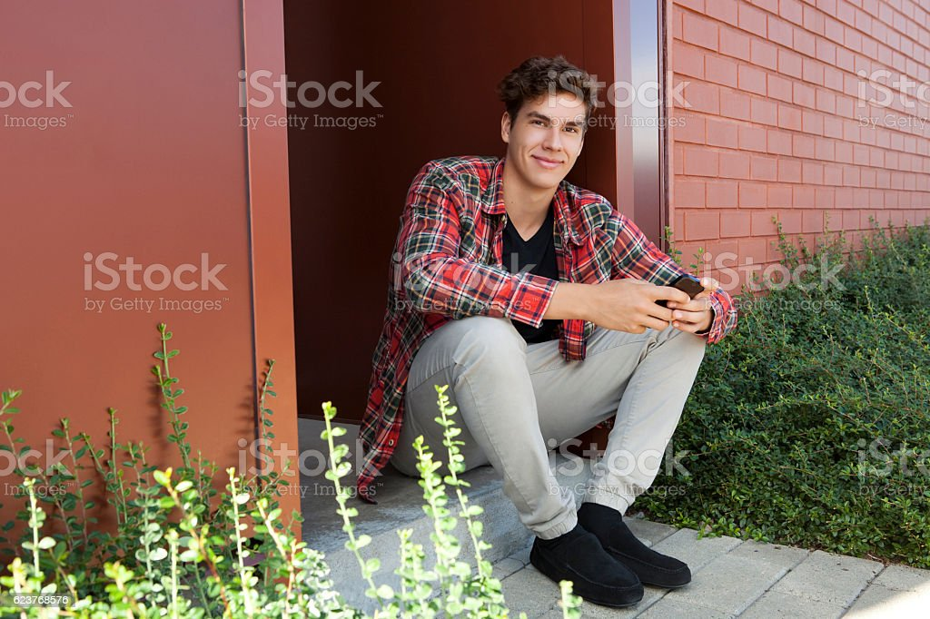 Full Length Portrait Of A Young Man Sitting Outdoor stock photo