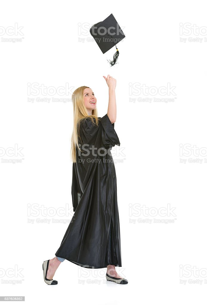 Full length portrait of happy young woman in graduation gown stock photo