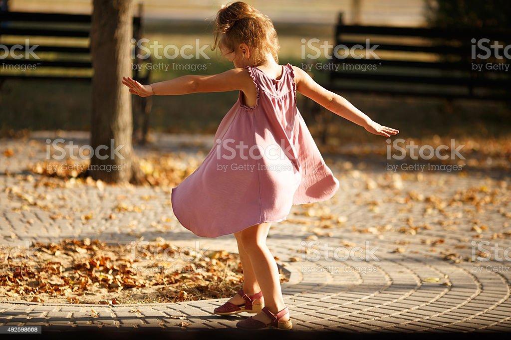 Full length portrait of little girl dancing in the park stock photo