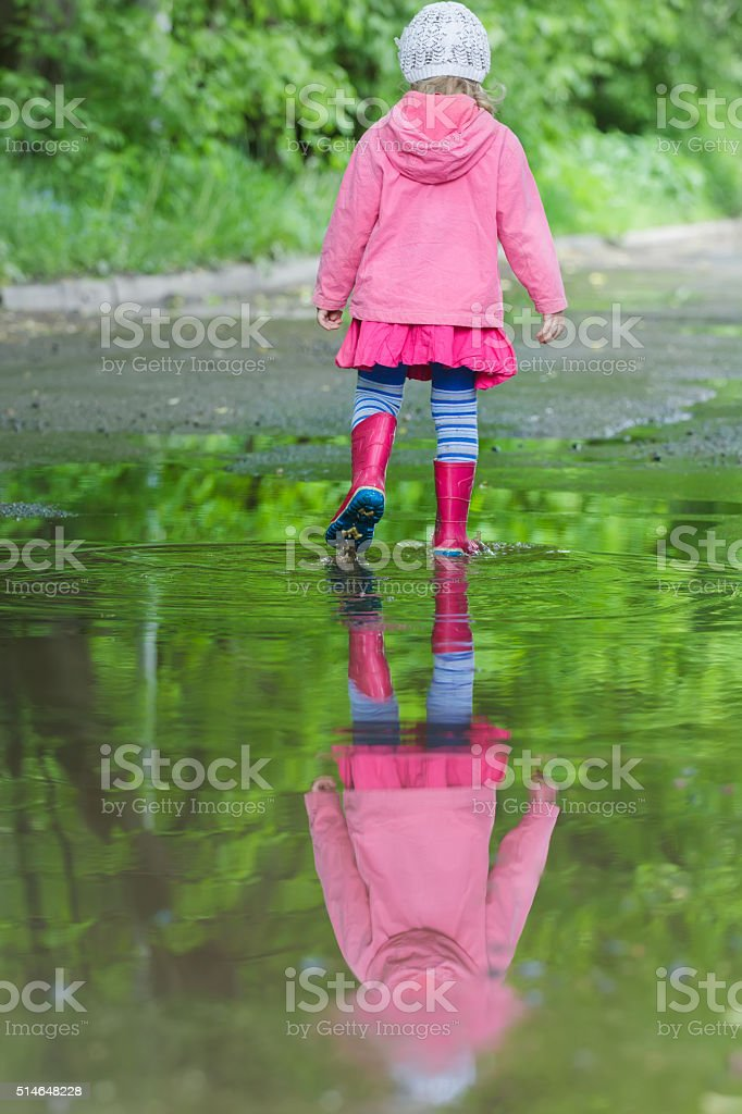 Full length portrait of little girl wearing red gumboots stock photo
