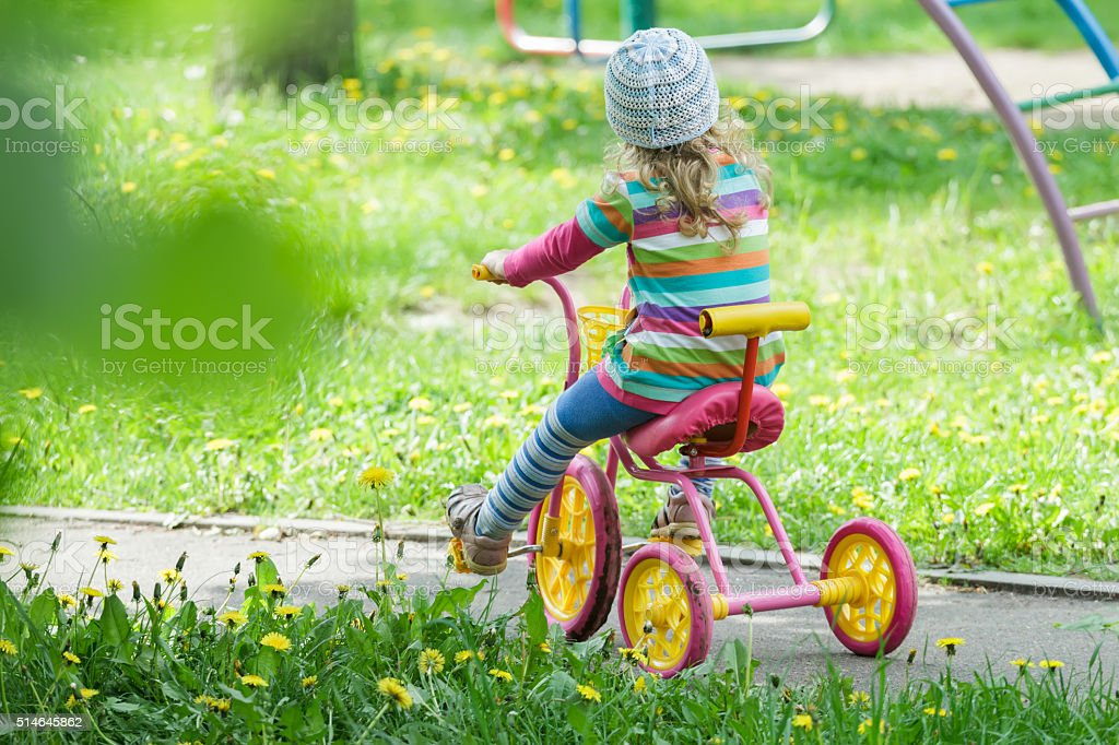 Full length portrait of preschooler girl riding kids tricycle stock photo