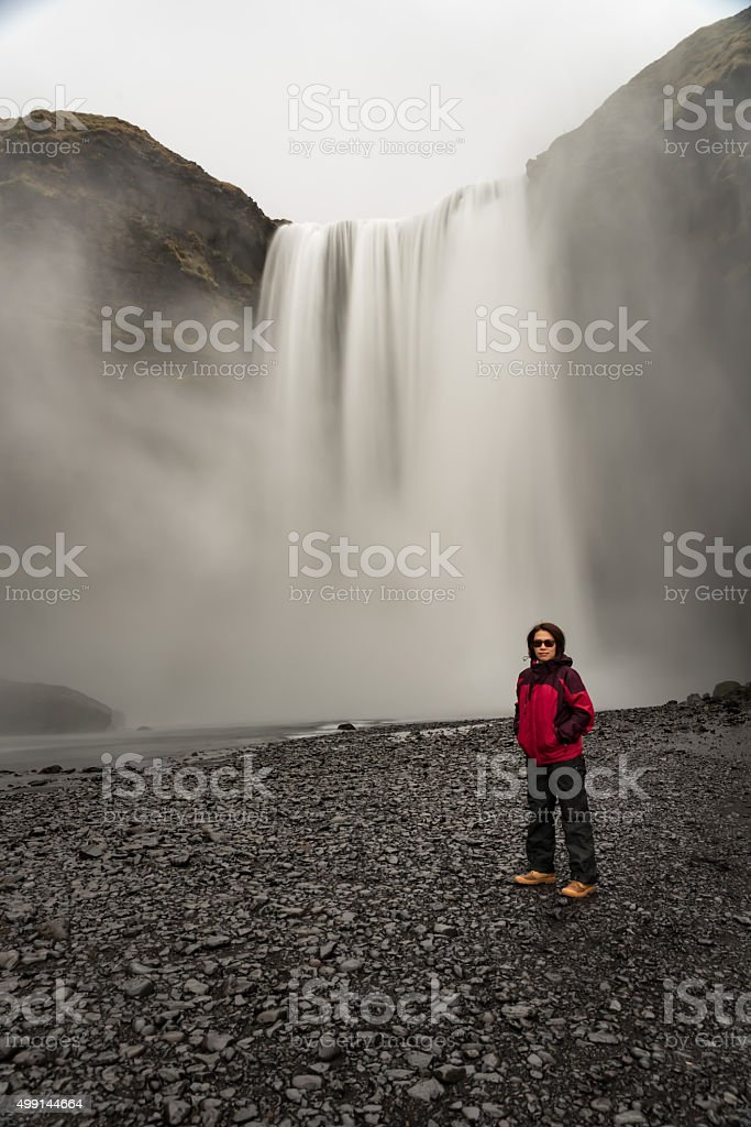 Full length portrait of woman stand in front ofwaterfall stock photo