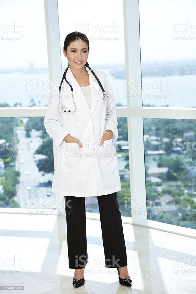 Full length portrait of young female doctor standing in office royalty-free stock photo