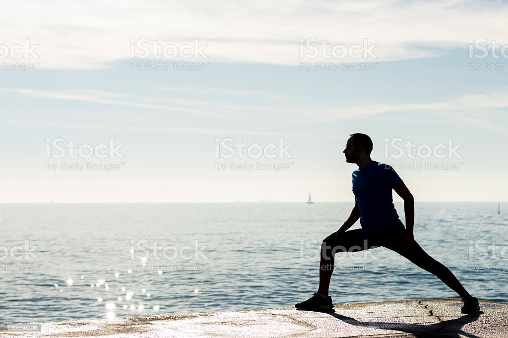 Full length silhouette portrait of a young jogger stretching stock photo