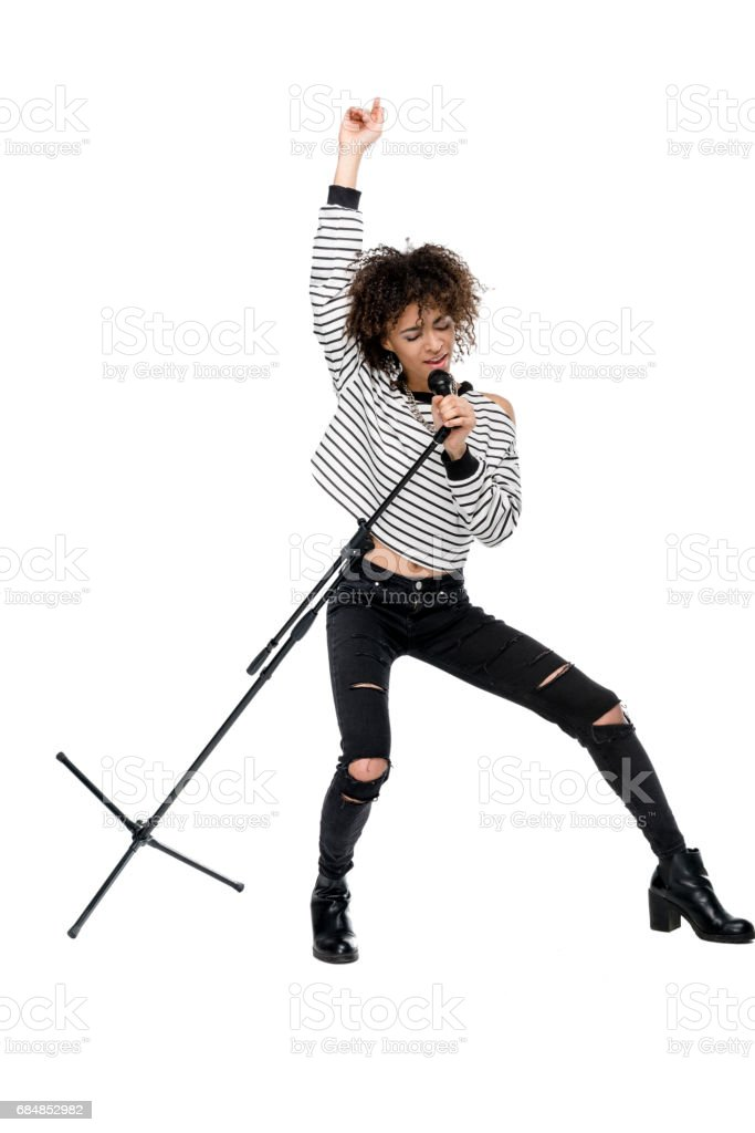 Full length view of beautiful young woman with microphone singing and gesturing isolated on white, heavy metal singer concept stock photo